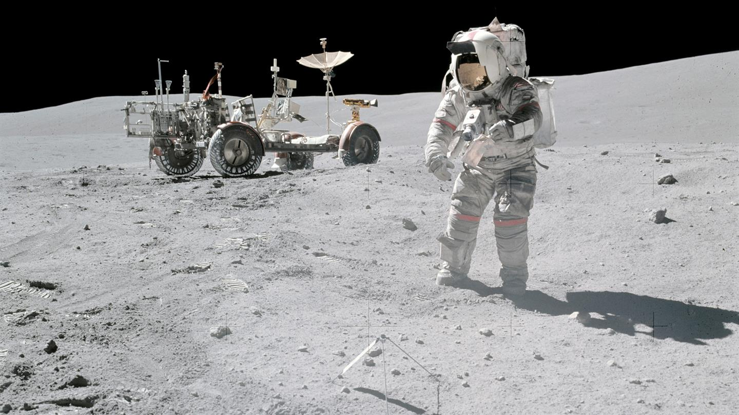 Apollo 16 Commander John Young on the moon in 1972. Lunar roving vehicle in background.